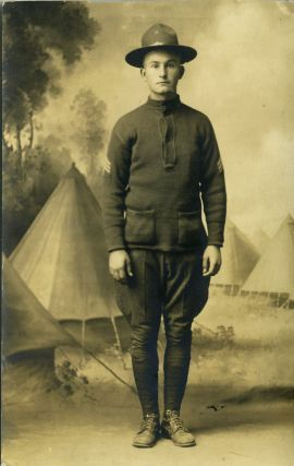 Postcard of World War I soldier, a studio shot in front a background scene ot conical pitched...